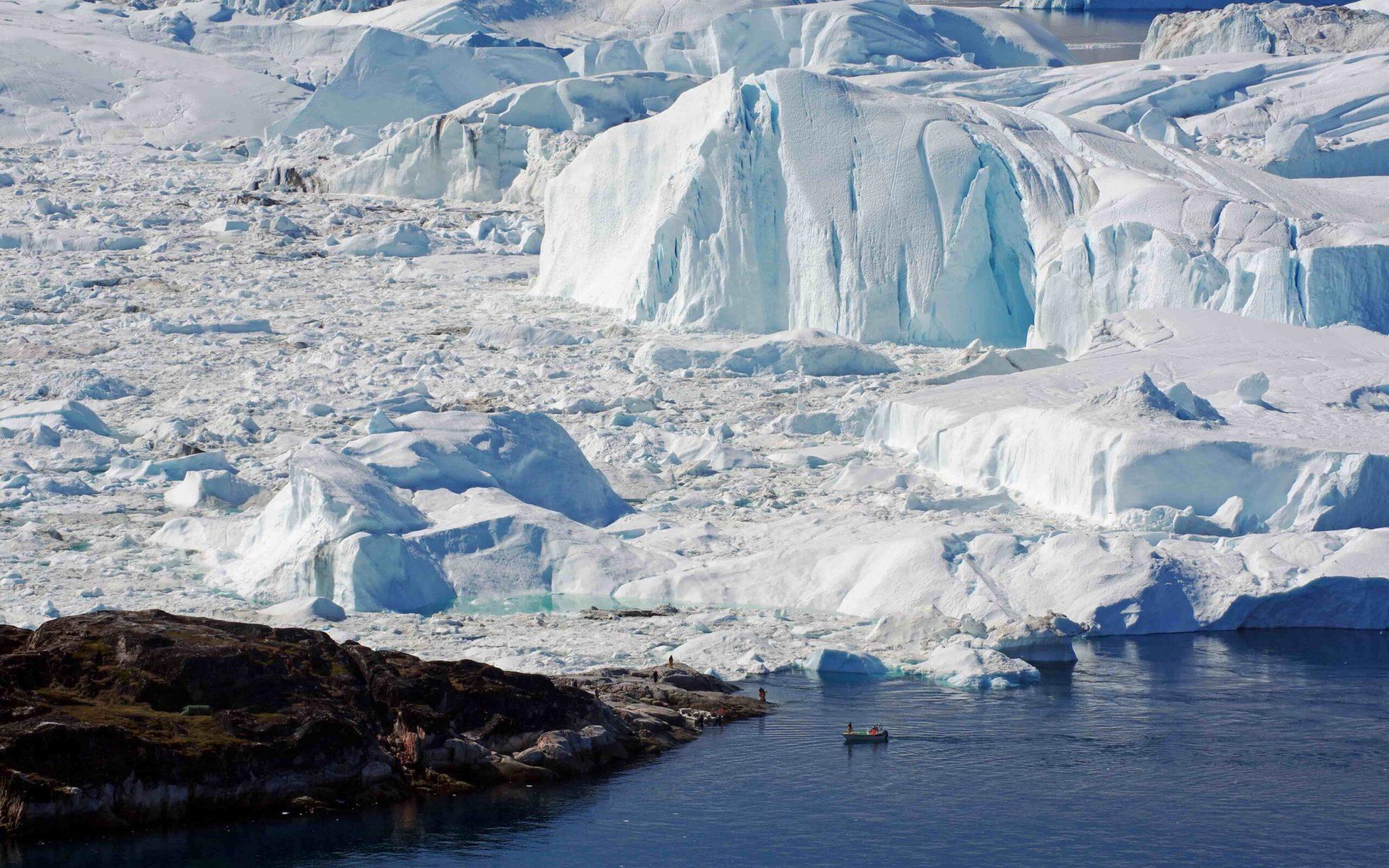 Local sailors come ashore amidst icebergs. Photo - Reinhard Pantke , Visit Greenland-min