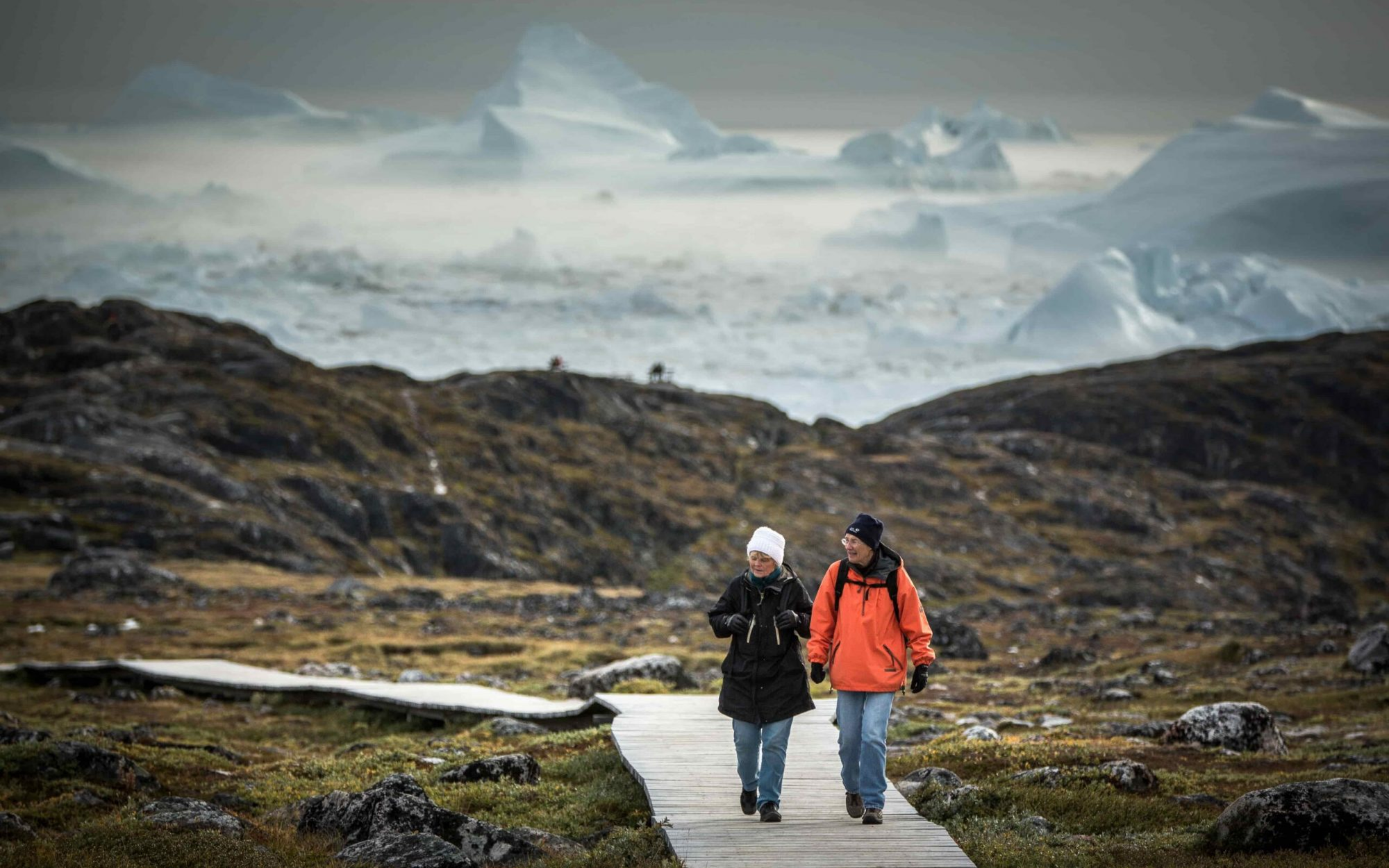 Two women on the boardwalk near Sermermiut with icebergs in the background in Ilulissat in Greenland-min